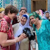 Pilgrims with traveller at Shah-i-Zinda, avenue of mausoleums, Samarkand | Richard I'Anson