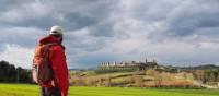 A walker admiring the hilltop town of Monteriggioni on the Via Francigena, Italy | Brad Atwal