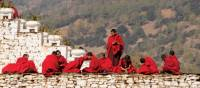 Bhutanese monks socialise along the monastery wall | Liz Light