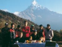 Young trekkers enjoy breakfast with local staff , the beautiful peak of Machapuchare in the backdrop |  <i>Sue Badyari</i>