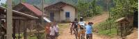 Family group cycling past Hmong women in Northern Laos |  <i>Kate Baker</i>