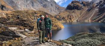 A trekker and guide pose in front of lake Om Tsho on the Bhutan Snowman Trek | Matt Brazier